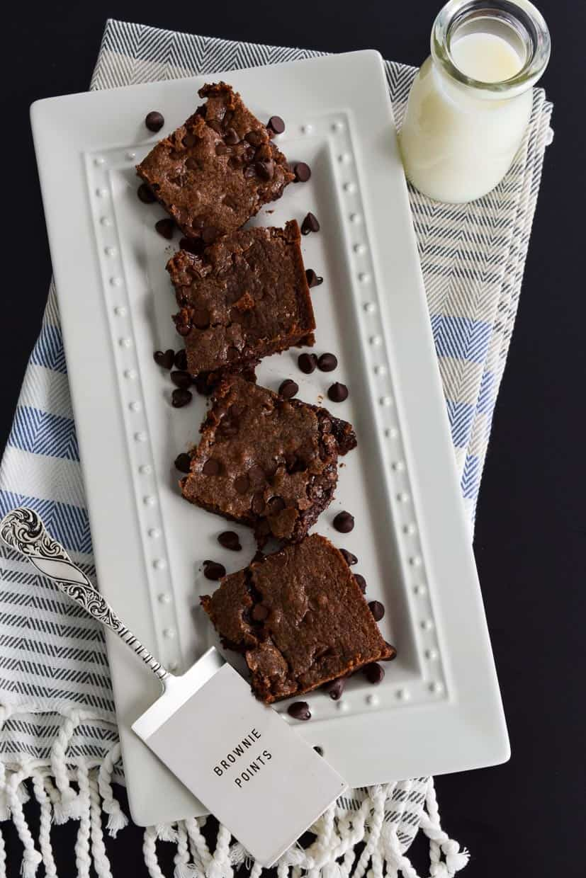 Chocolate Chip Brownies on white platter on top of striped kitchen towel next to glass of milk overhead shot