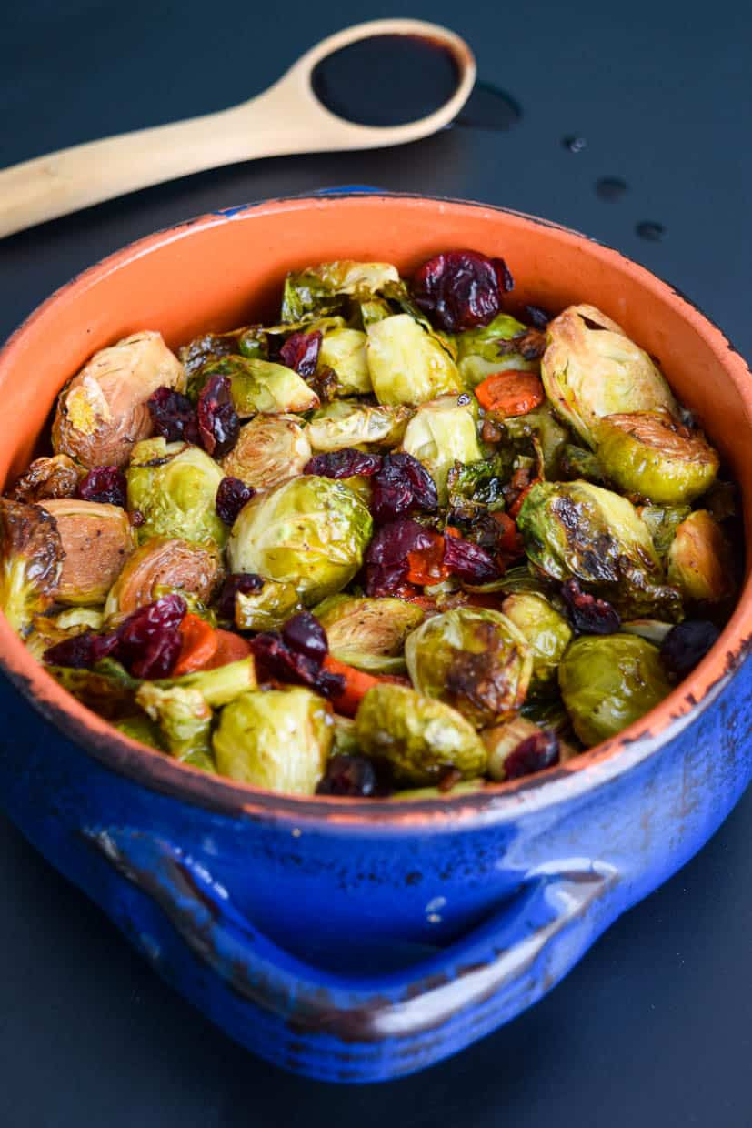 balsamic roasted Brussels sprouts with carrots and dried cranberries in blue and orange bowl