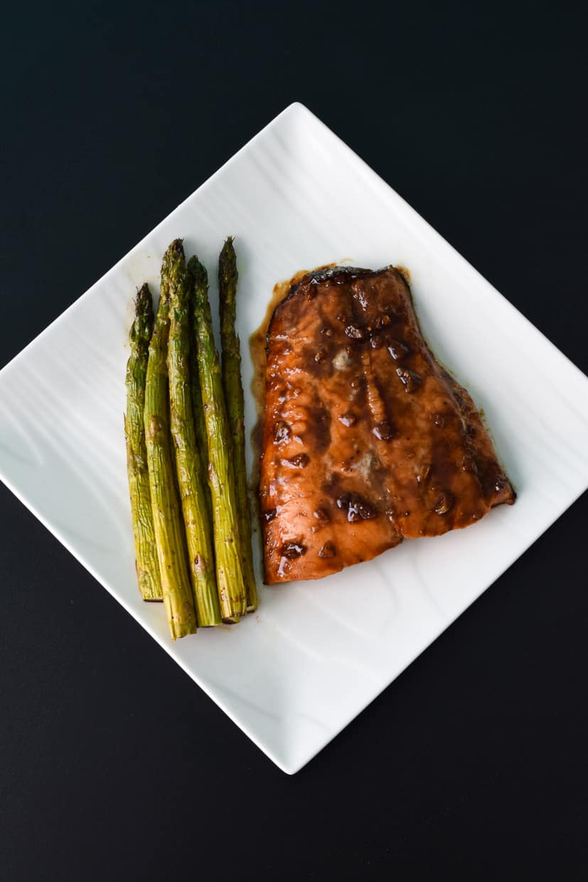 Asparagus served with roasted salmon on white square plate overhead shot