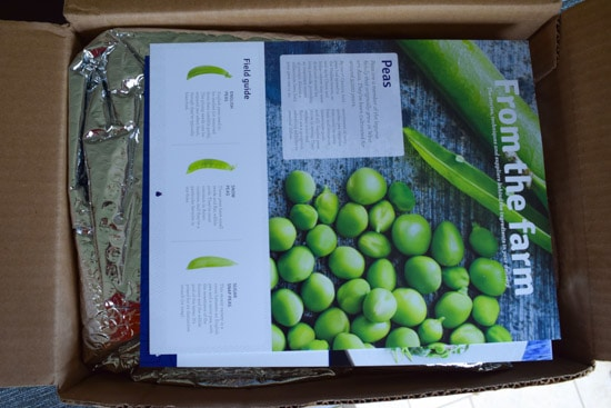 blue apron box being opened showing info card about peas overhead shot