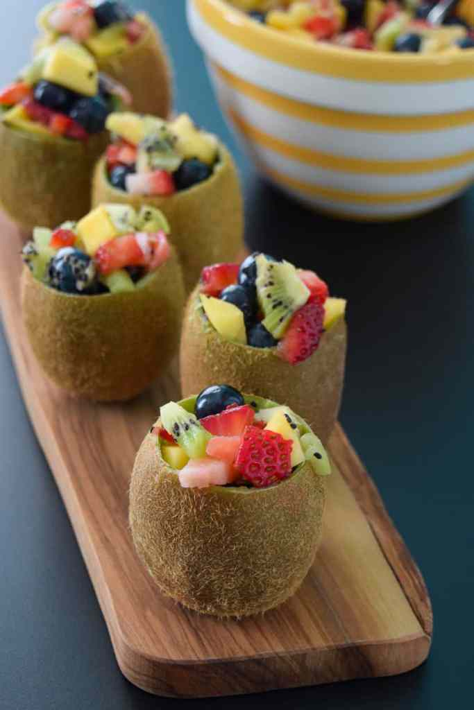 Close up view of tropical fruit salad in kiwi cups on wooden platter