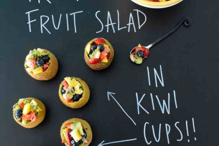 Tropical Fruit Salad in Kiwi Cups with title written on black chalkboard