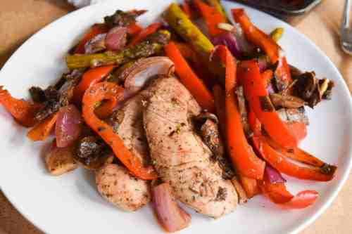 balsamic chicken and veggies on white plate close up view