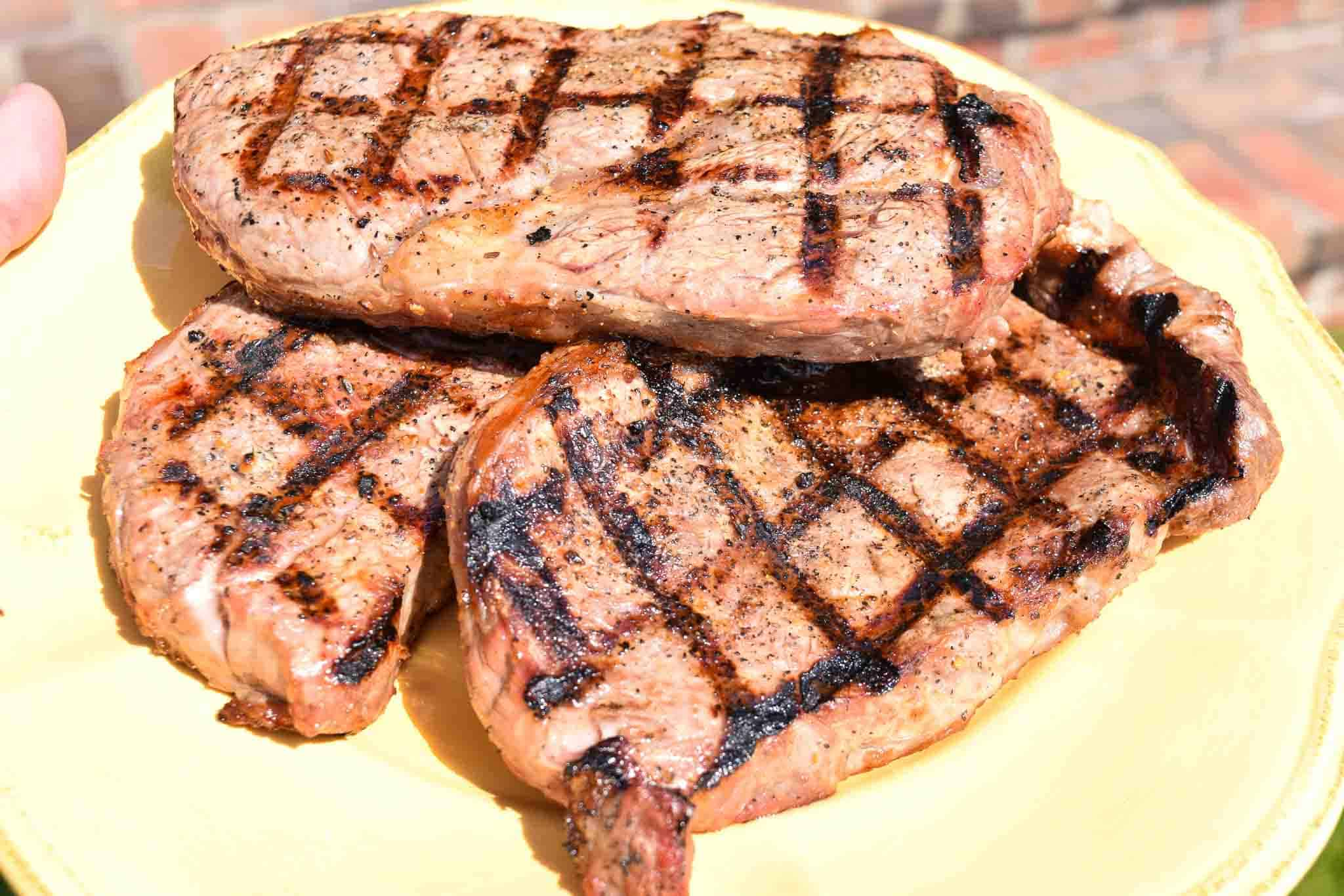 Steaks stacked up on yellow plate ready to be served