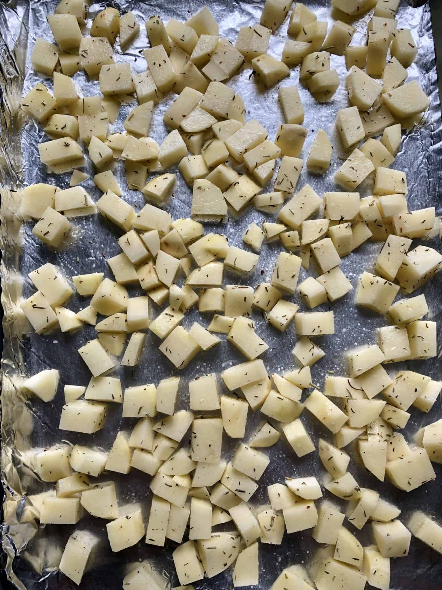 diced potatoes uncooked on baking sheet