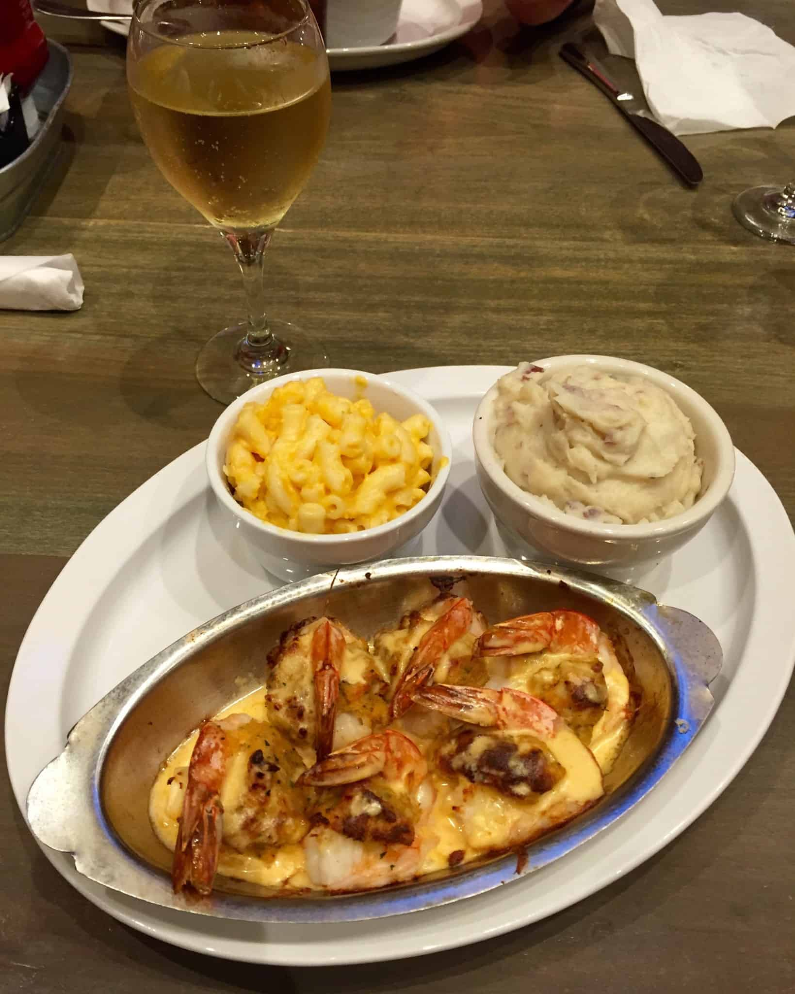 Plate of stuffed shrimp mac and cheese mashed potatoes and a glass of wine