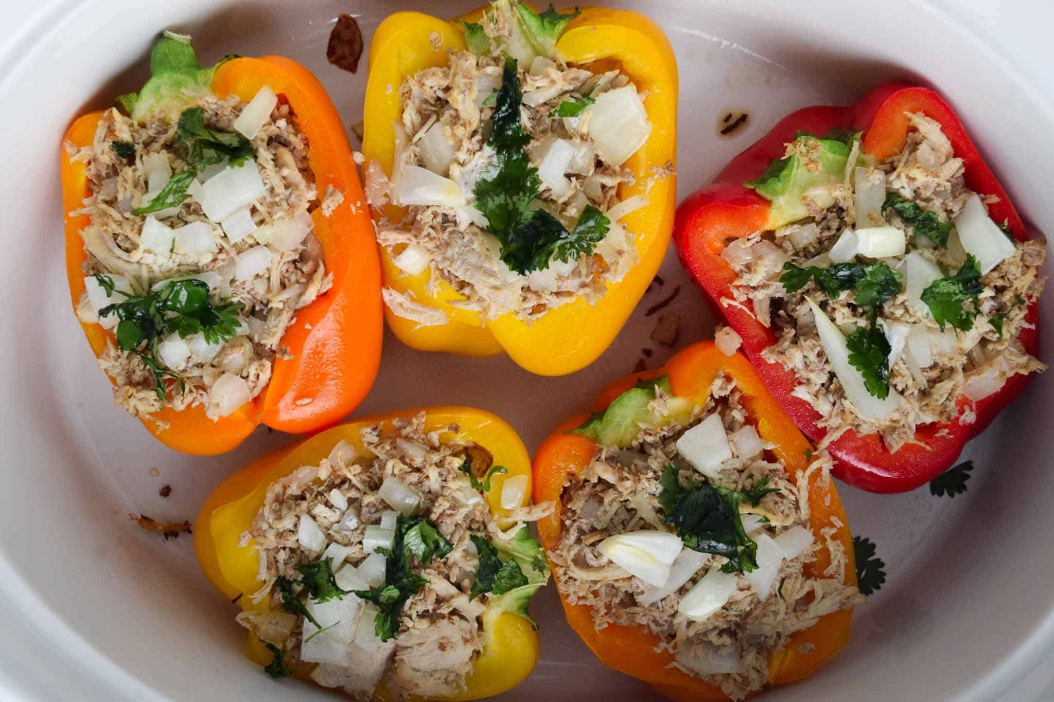 cooked chicken stuffed peppers in white dish topped with cilantro overhead shot