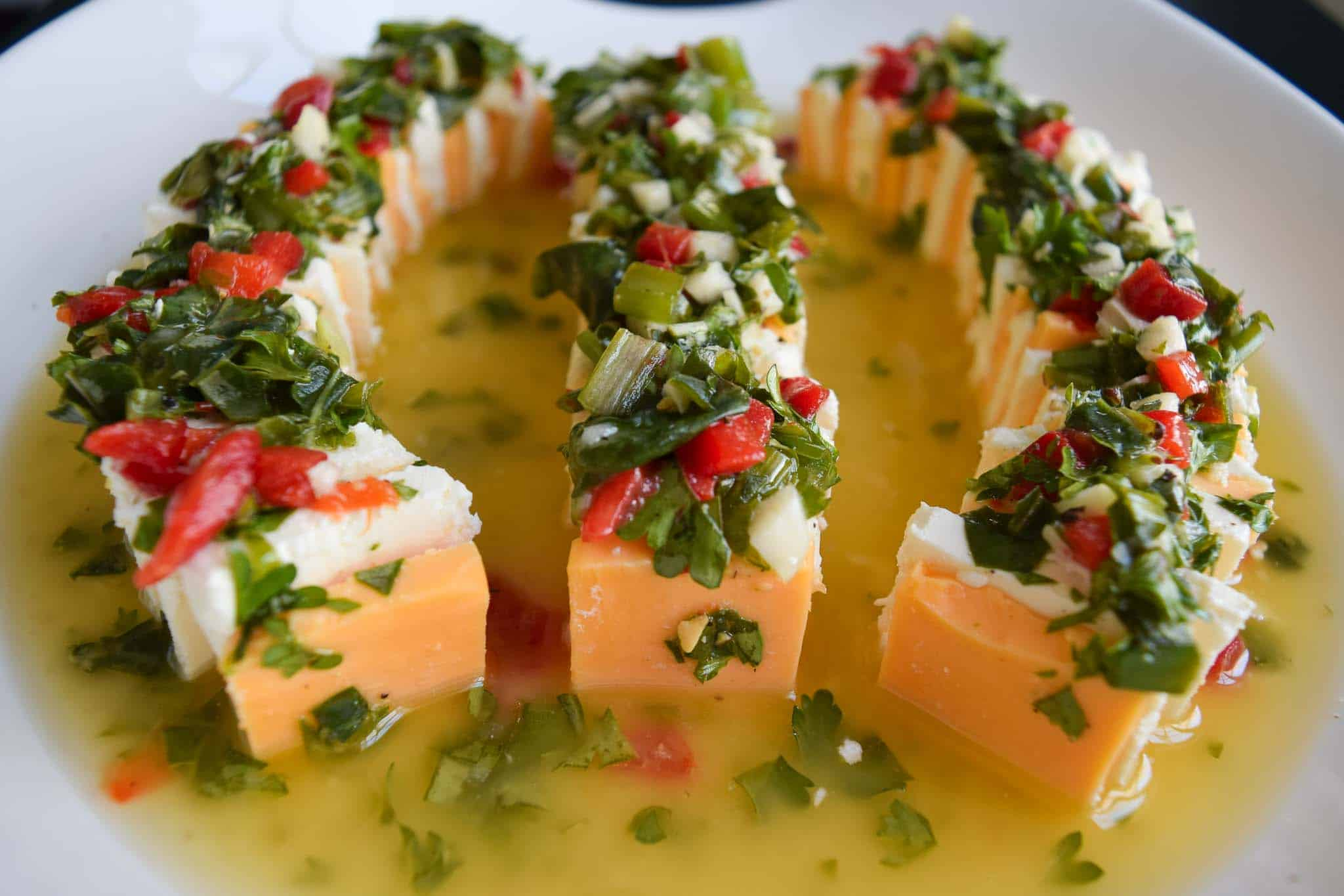 marinated cheese slices sitting in white dish close up view