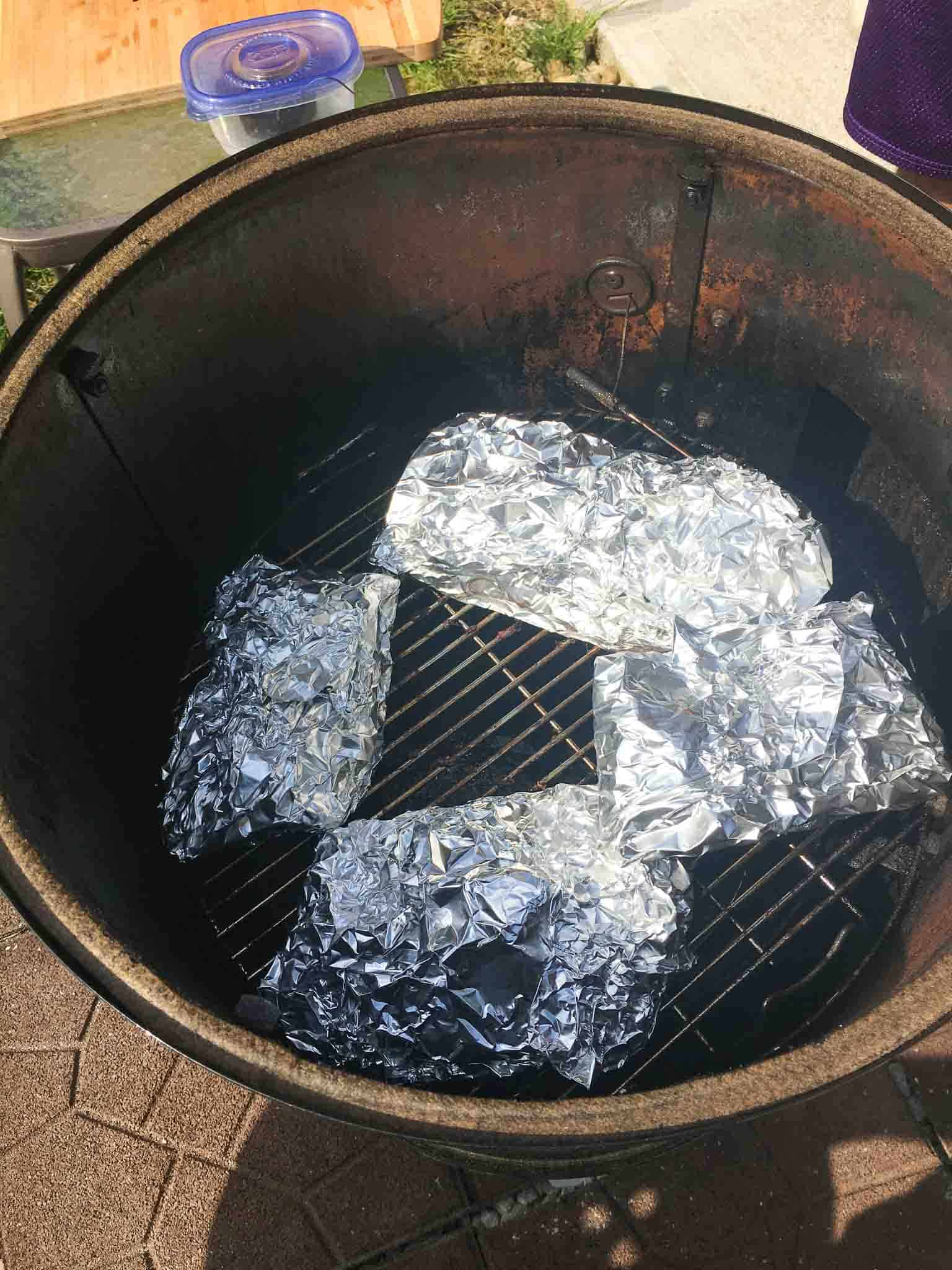 ribs wrapped in foil inside of weber grill overhead shot