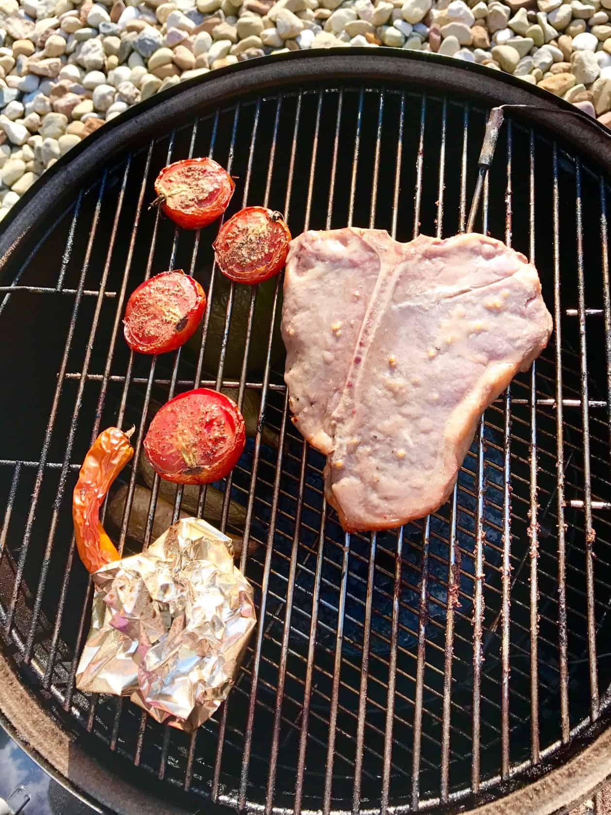 Steak with vegetables on weber grill overhead shot