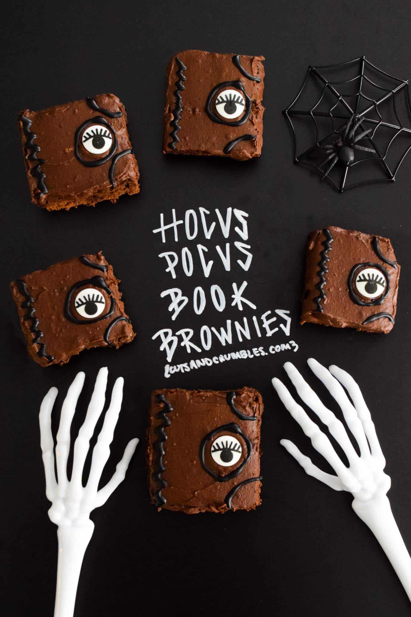 Hocus Pocus Book Brownies with title written on chalkboard and halloween skeleton hands reaching for brownies