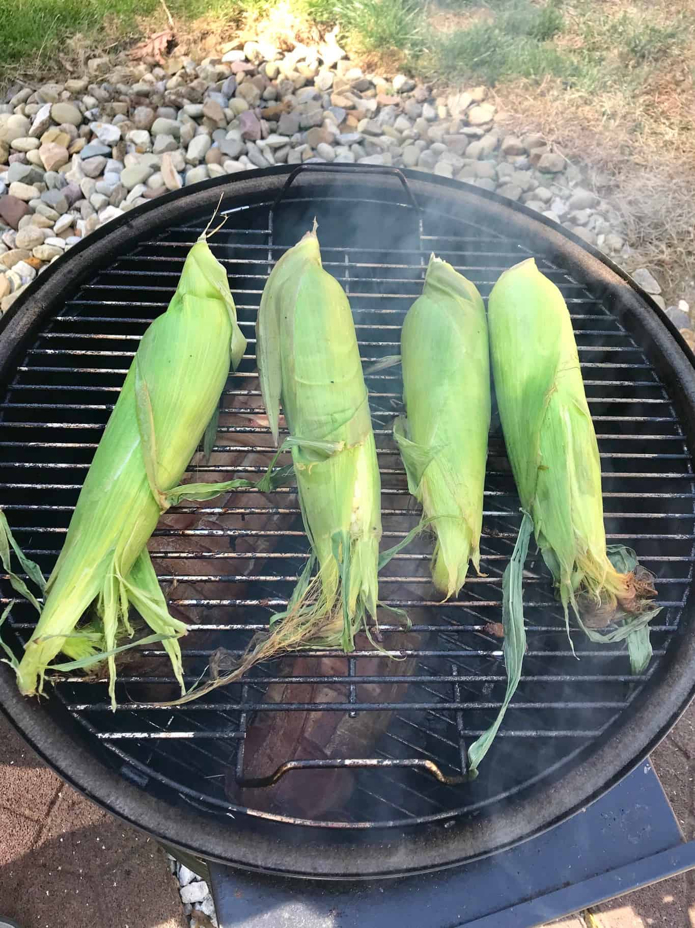 Corn on the cob in husks on weber grill