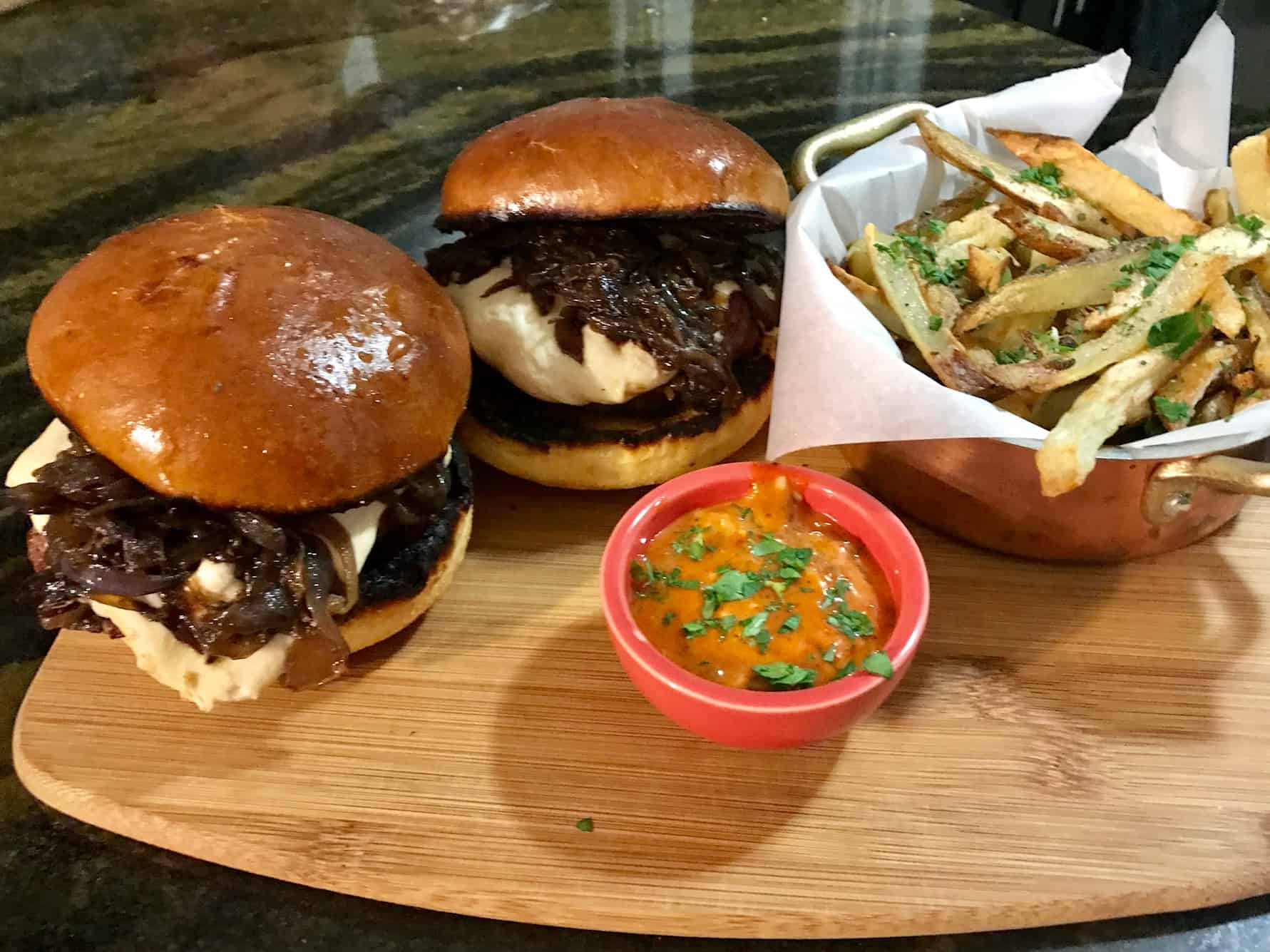 Home Chef Swiss Burgers on cutting board served with fries and small bowl of sauce