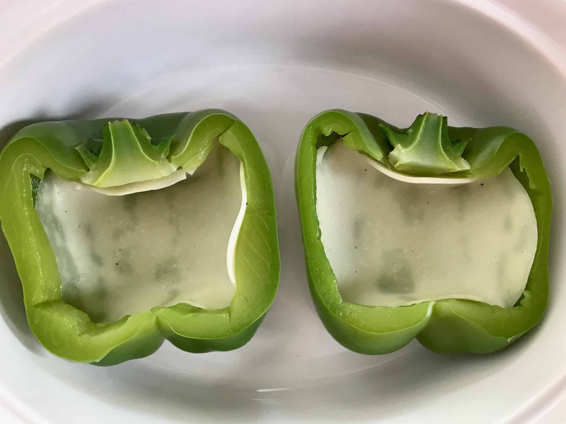 Green pepper sliced in half with provolone cheese inside in white bowl overhead shot