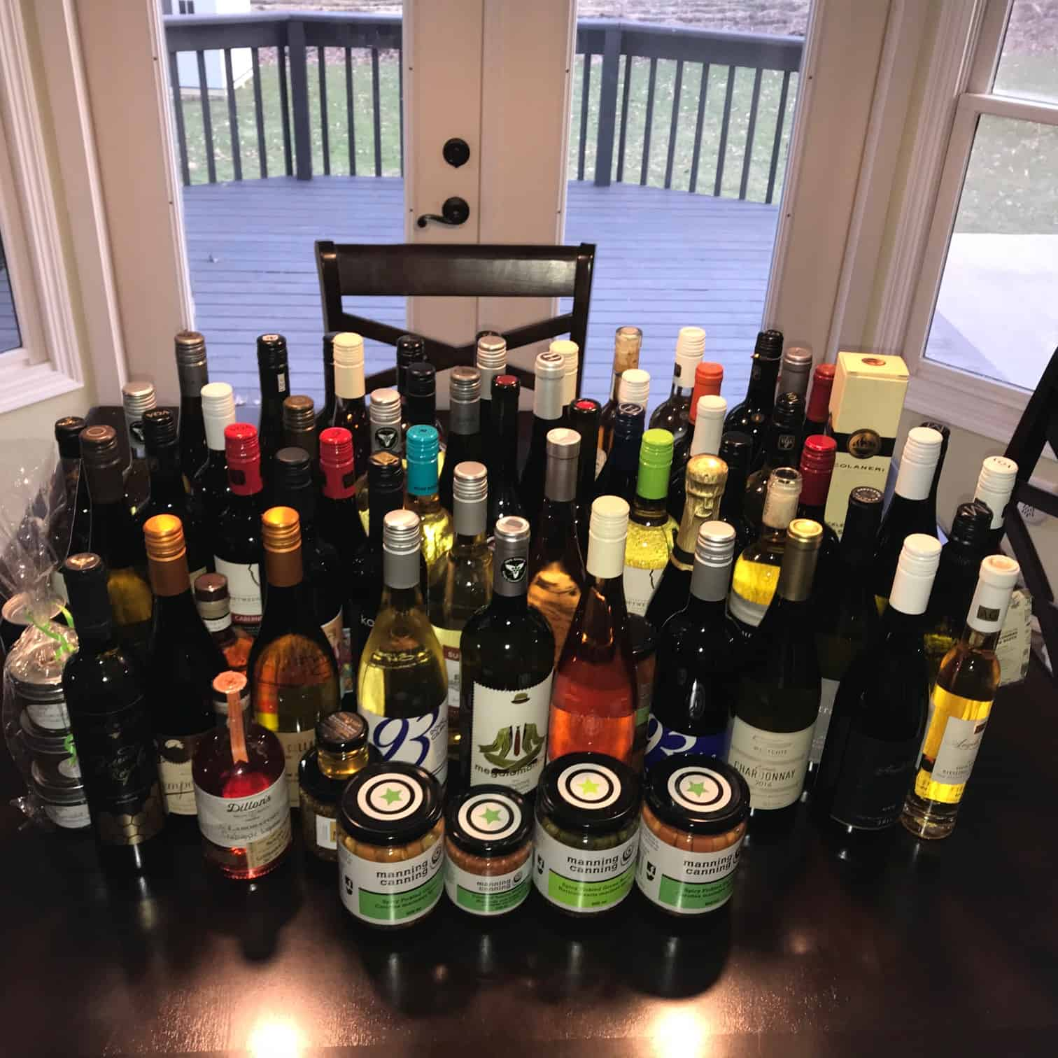Giant collection of wine bottles lined up on kitchen table