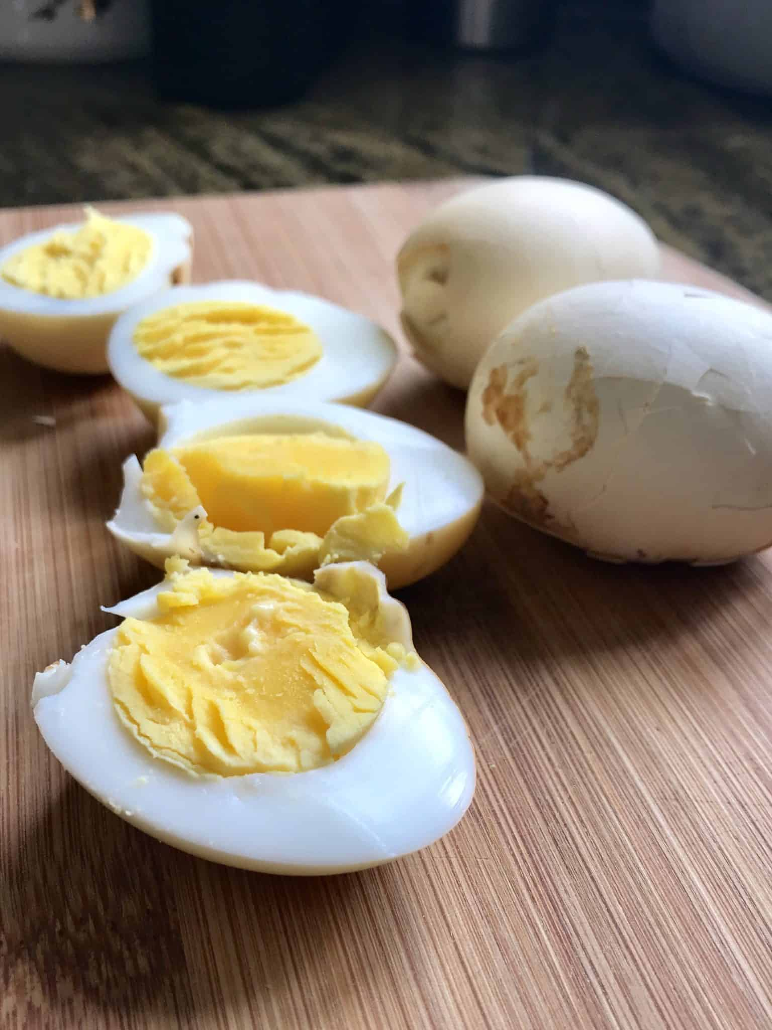 Smoked Eggs sliced in half sitting on wooden cutting board close up view