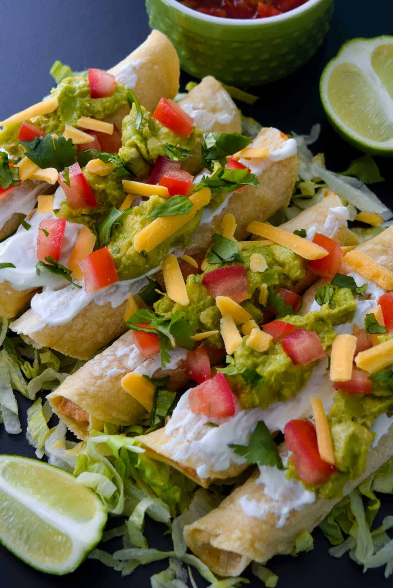 Baked Chicken Taquitos with toppings ready to be served close up