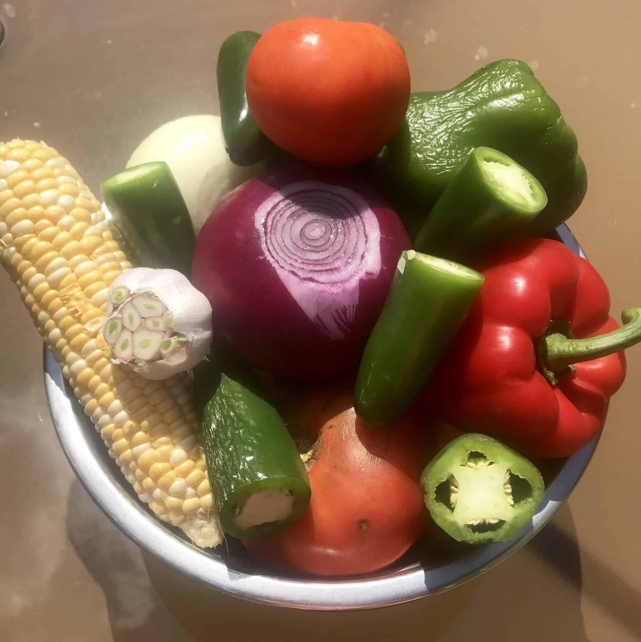 Fresh vegetables to be used in salsa piled up in a bowl