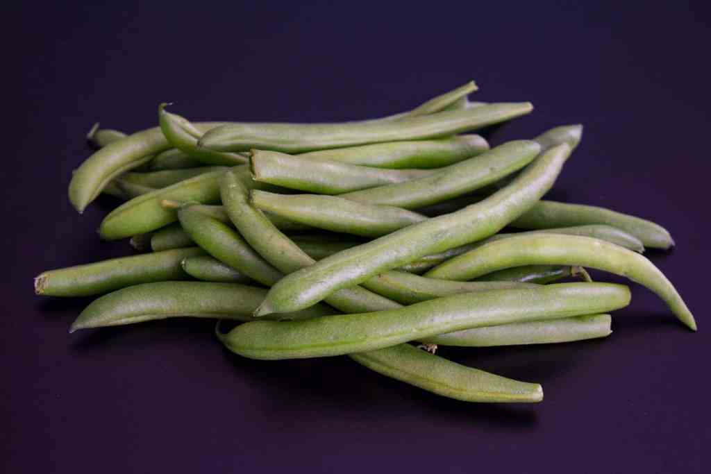 green beans on black background