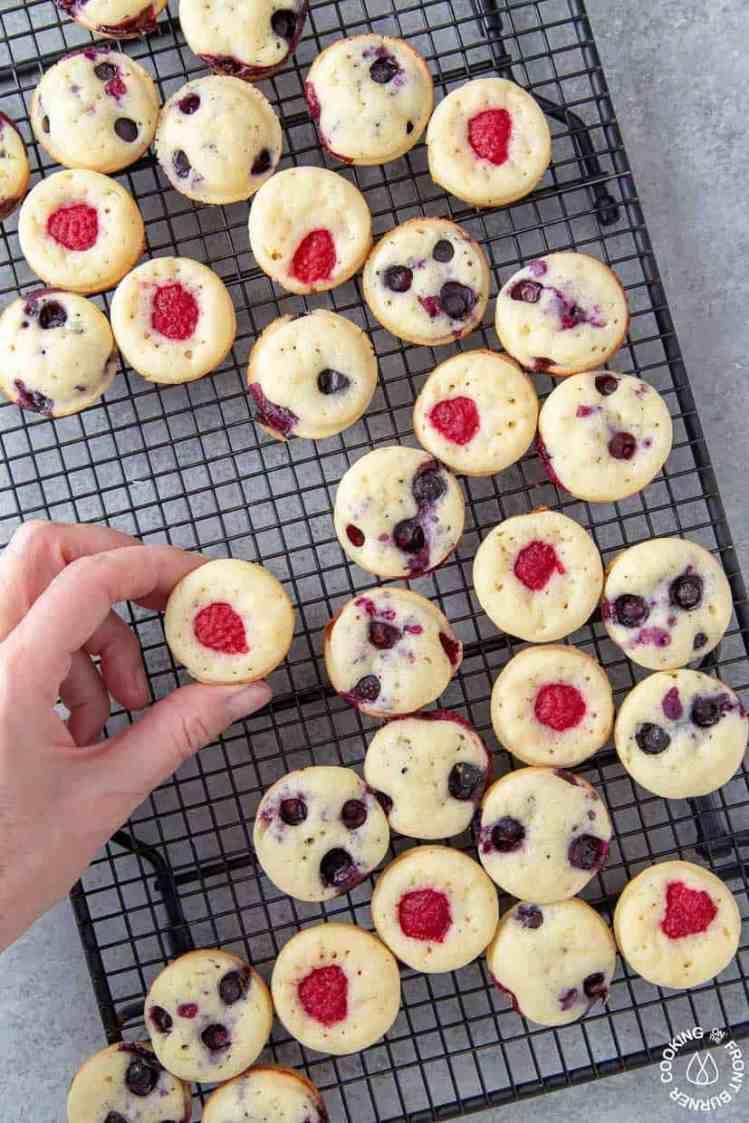 hand grabbing mini pancake muffin off cooling rack