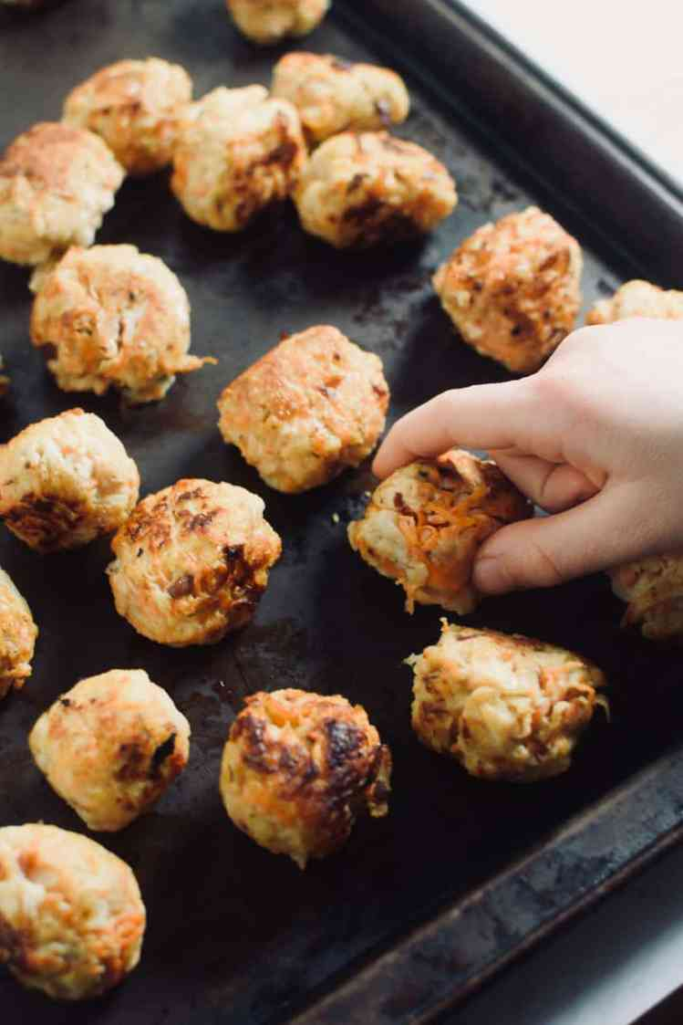 child hand grabbing chicken meatball off black pan