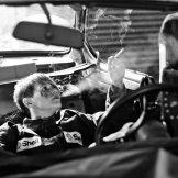 Foto zum Thema Auszeit: eine Frau sitzt in einem ausgeschlachteten Auto und raucht sich ganz entspannt eine Zigarette