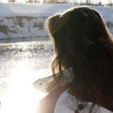 Das atemraubende Silentium: dieses Bild zeigt eine junge Frau die im Winter auf eine glitzernde Wasseroberfläche eines Flusses blickt