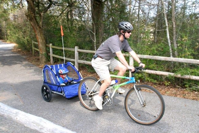 Dad pulling son in trailer - Black Friday deals on kids bike trailers
