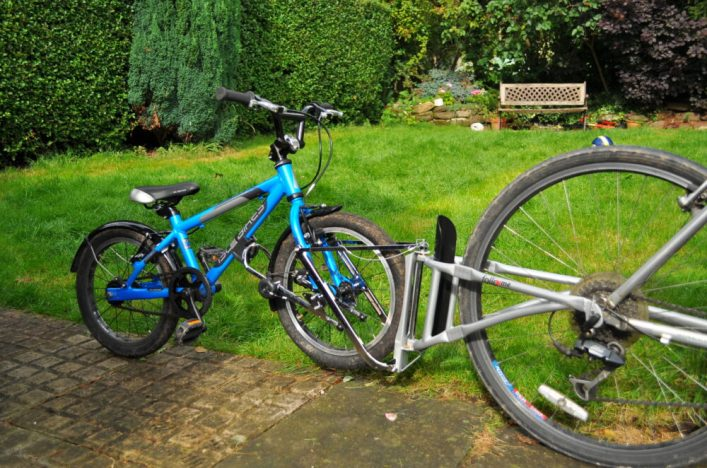 FollowMe Tandem cycle hitch in place with childs bike being towed behind the adult bike