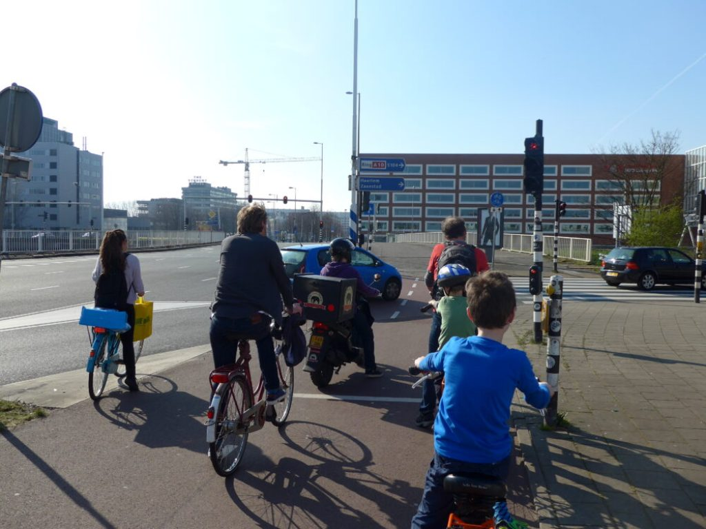 9 year old boy ycling on the segergated paths Amsterdam. If you're wanting to hire a kids bike in Amsterdam read this excellent guide to help you make the correct choice