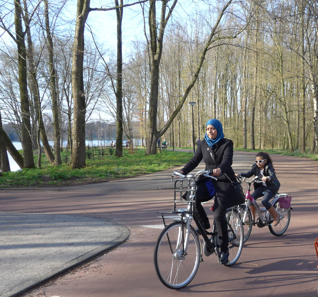 Photo of woman in headscarf and child cycling bikes