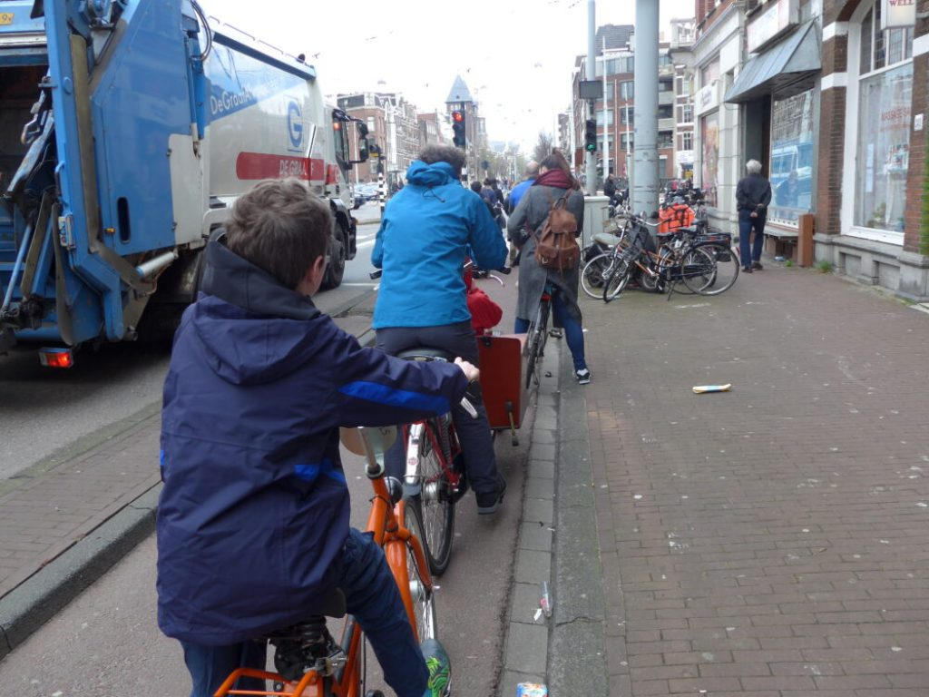 Cycling safely alongside a lorry in Amsterdam, Holland. If you hire a kids bike in Amsterdam it's easy to get around town to see all the sights