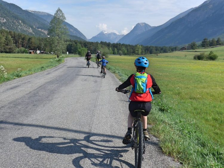 Family cycling in the Vallée de la Clarée in the French Alps - riding with the valley stretching out in front