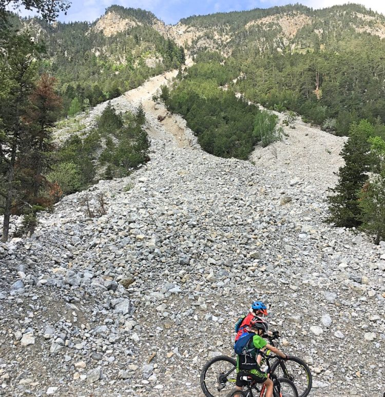 Family cycling in the Vallée de la Clarée in the French Alps - rock fall down towards river Claree close to Val-Des-Prés