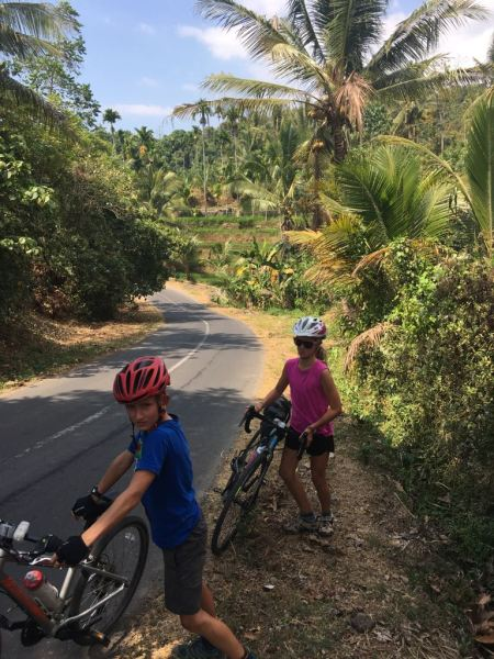 Pushing bikes up the hill in Sembalum Valley, Lombok, Indonesia