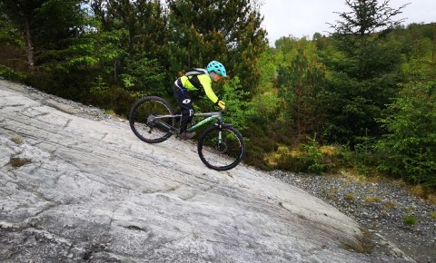 Girl riding downhill at Fort William mountain bike trails