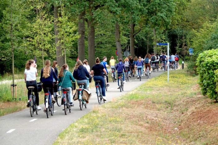 Teenagers cycling safely to school on protected intrastructure