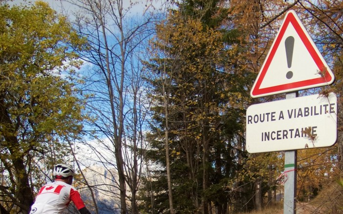 Unpaved road begins with a warning