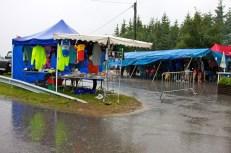 Het is noodweer op de Col de Manse. Het onweer is inmiddels gestopt, maar de regen houdt onverminderd aan. De meeste mensen zitten in hun camper/auto/bus, of proberen zoals op de foto te zien te schuilen onder een tentzeil bij het restaurant op de top. (© 2011 Laurens Alblas / Cyclingstory.nl)