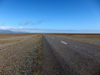 Lång rak väg på längs Islands sydkust. Solsken