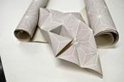 Papier peint aux motifs géométrique plié en structure à géométrie variable.