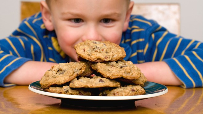 Boy looking at a plate of cookies showing willpower