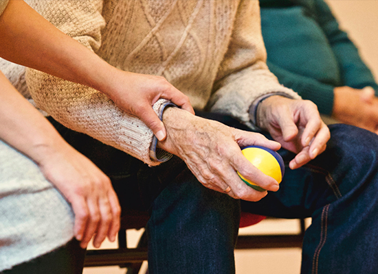 Younger person holding the arm of an older person who is holding a ball