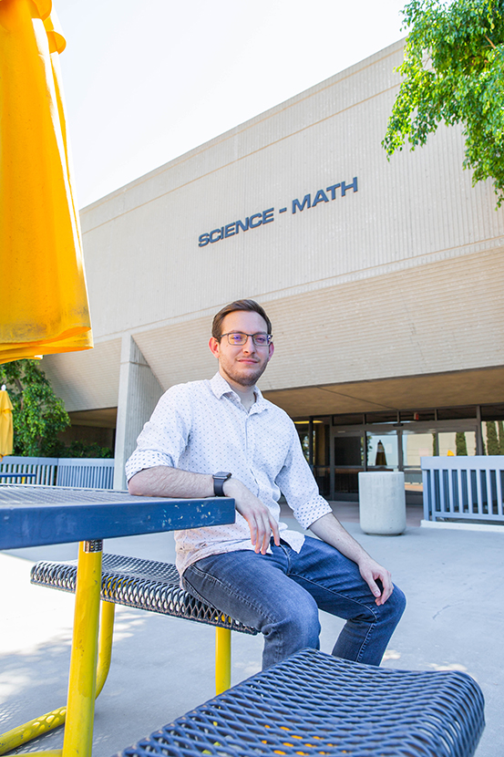 Student Francisco Cornejo-Garcia sitting in front of the Science building