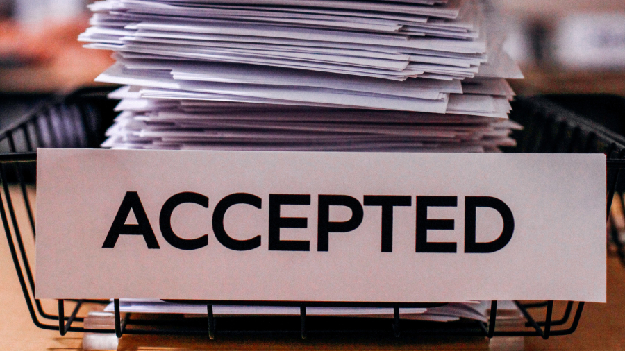 "Stack of papers in bin labeled ""Accepted"""