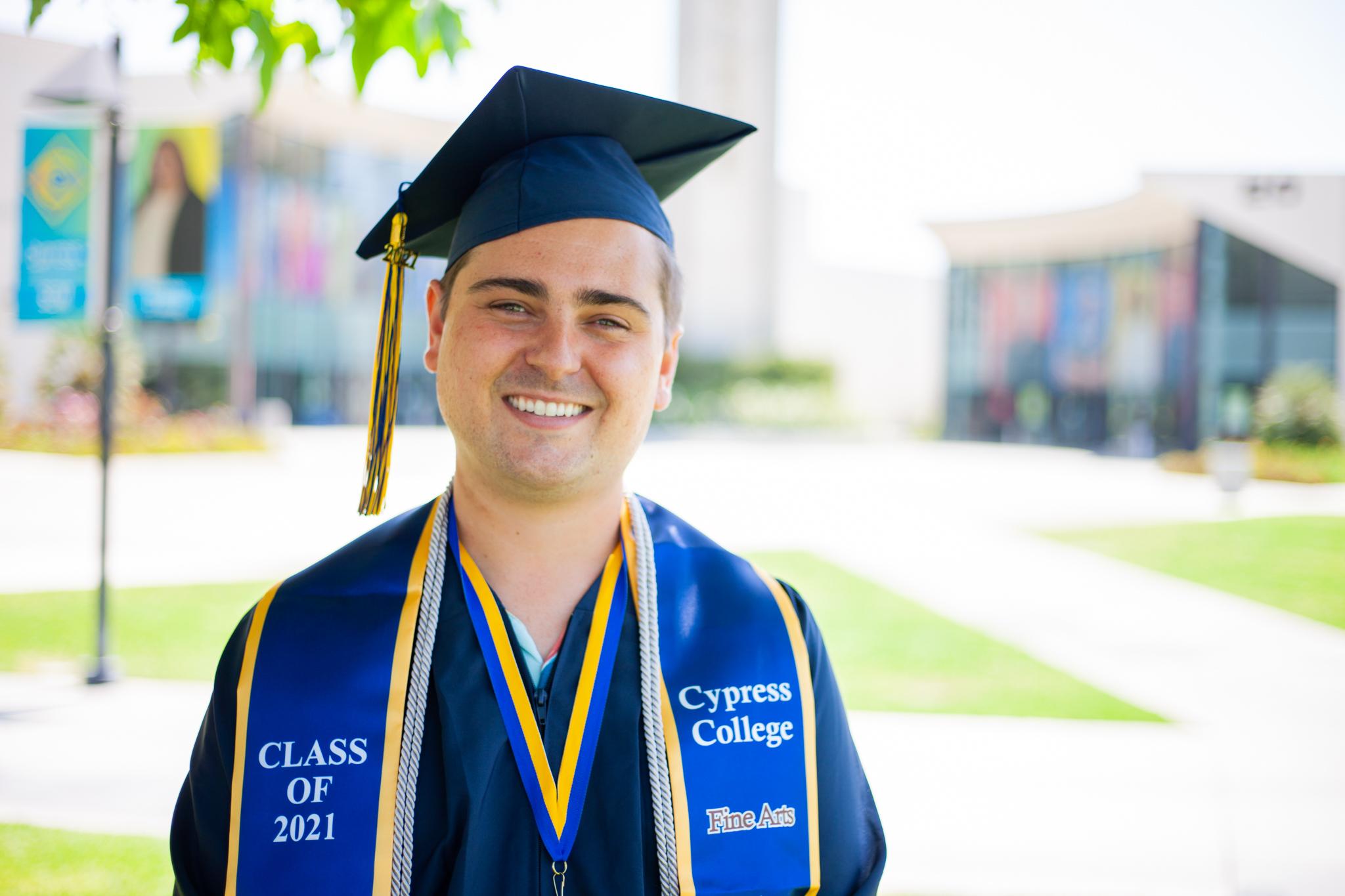 Film student Paul Scott poses in front of the campanile in graduation regalia.