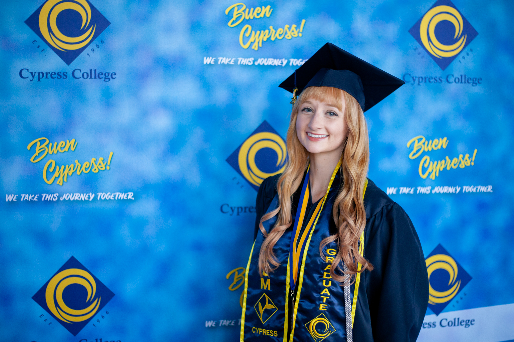 SEM student Lia Thompson poses in front of blue backdrop.