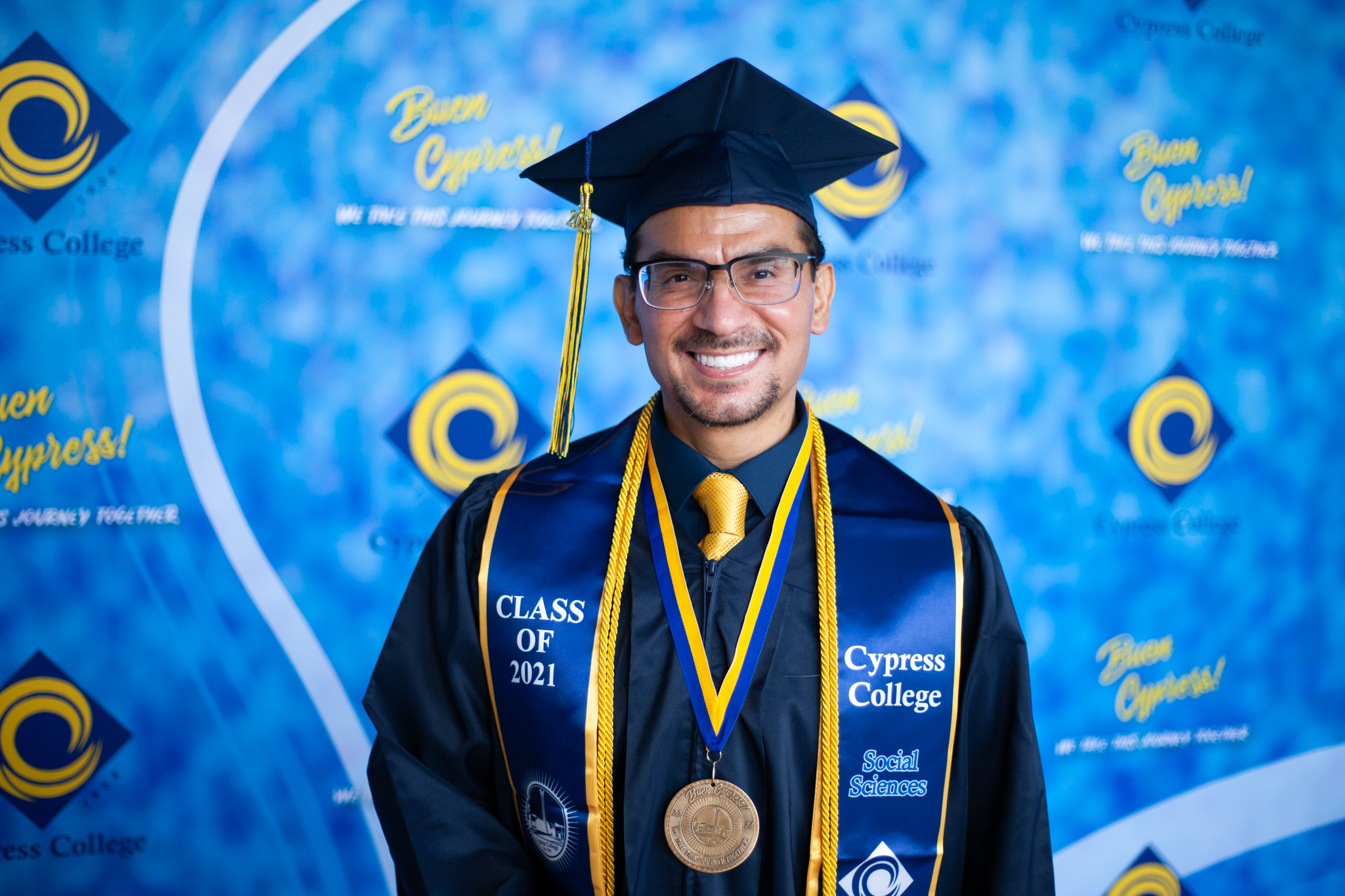 Social Sciences student Wilfredo Carrasco poses in front of blue background.