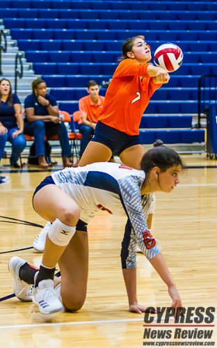 Makensie Garner (7, orange) sets the ball as Katie Kessler (foreground) recovers from digging the ball during the Bears' 2018 season opener at CFISD HS #12 High School, Aug. 7, 2018. (Cypress News Review photo by Creighton Holub)