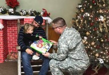 Texas State Guard member gives a toy to a child in a hospital. (TXSG photo)
